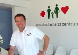 Internist Dr. Andreas Leonhard aus Paguera Portrait vor Praxislogo
