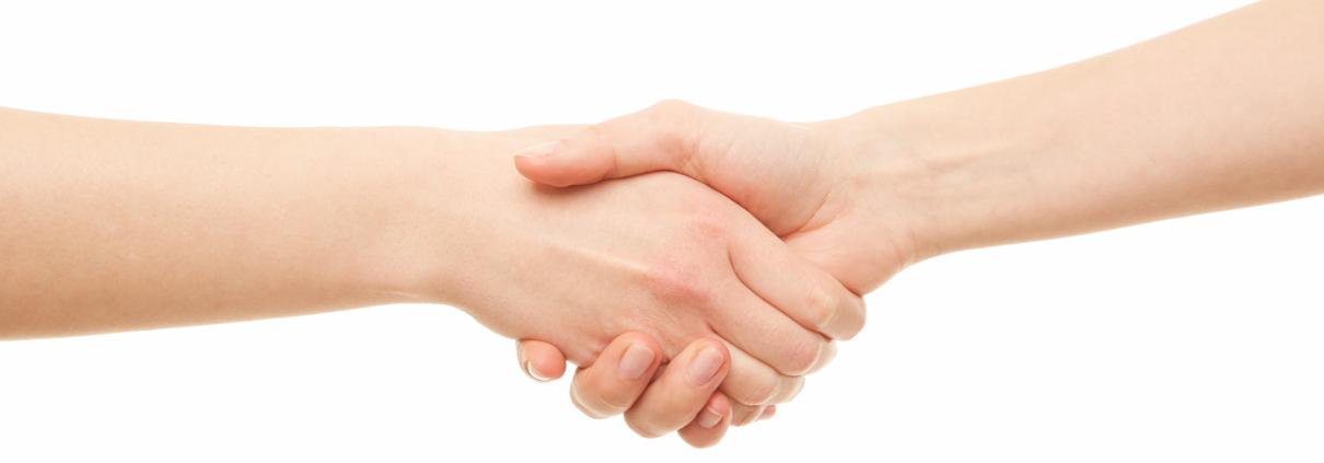zwei Frauen reichen sich vor weißem Hintergrund die Hand