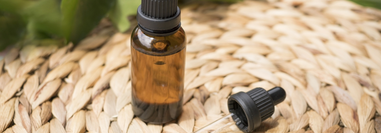 Fläschchen CBD Öl auf einem Bast Untersetzer Pipette liegt daneben Öl sichtbar